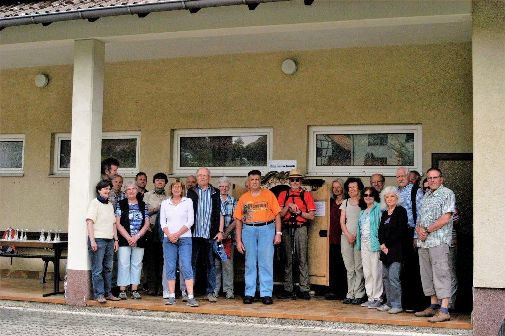 Etwa 20 Erzbacher Bürgerinnen und Bürger vor dem Dorfgemeinschaftshaus; im Hintergrund der Bücherschrank