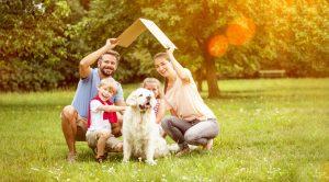 Vater, Mutter, zwei Kinder und ein Hund mit Pappdach über dem Kopf auf grüner Wiese