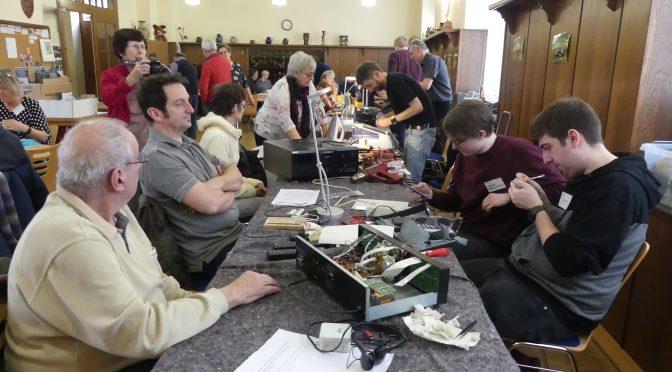 Blick über den Adlersaal; im Vordergrund Tisch mit Werkzeug; rechts junge Männer, die Gegenstände reparieren; links ältere Männer, die auf Reparatur warten, mit draufgucken; im Hintergrund weitere Tische, an denen repariert wird; Menschen stehen in Gruppen beieinander und unterhalten sich
